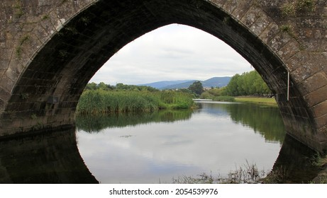 Ponte de Lima, Portugal - July 20, 2021: View through the arch of the medieval stone bridge over the river Lima