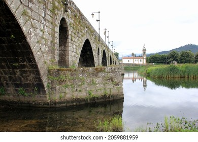 Ponte de Lima, Portugal - July 20, 2021: Medieval stone bridge over the Lima River, 18th-century Church of Santo Antonio da Torre Velha in the background on the opposite side of the river