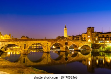 The Ponte Pietra has the Adige River at night. The Campanile di Santa Anastasia Verona is visible in the background.