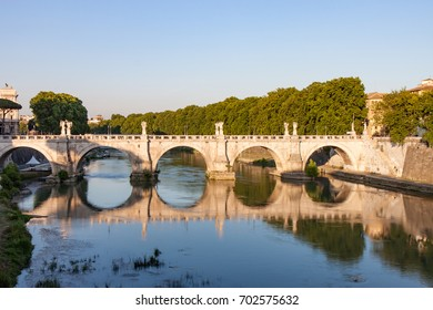 Ponte Sant'Angelo Reflecting the Tiber River in Rome Italy at Sunset. Known as the Bridge of Angels, it features 10 statues of angels and dates from134 AD.