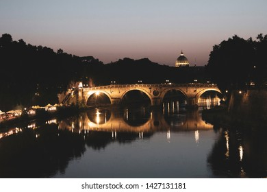 The Ponte Sisto bridge in Rome over the Tiber river at night. It is nicely lit at night and in the distance there is a basilic visible. At the riverside there is a market.