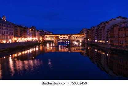 Ponte Vecchio bridge in Florence at night time with city lights reflecting in Arno river.