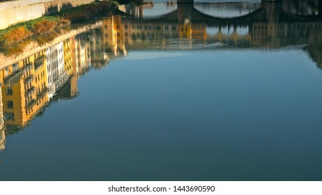 Ponte Vecchio bridge and Florentine houses reflection on water, Florence, Italy