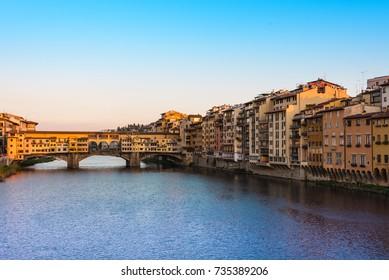 The Ponte Vecchio bridge over the Arno River at sunset.