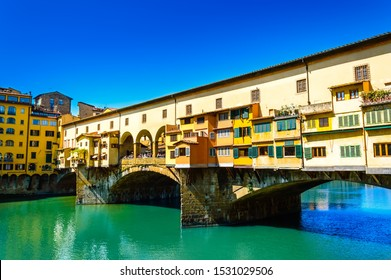 Ponte Vecchio or Old Bridge over the Arno River in Florence, Italy. Arch bridge with jewelery and art shops and colorful buildings is a famous tourist attraction