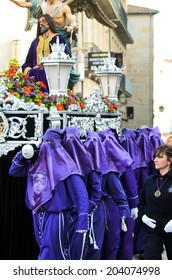Pontevedra , SPAIN - APRIL 17, 2014 : Members of a hooded brotherhood , loaded with a step of Easter, in one of the processions through the city.