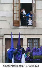 PONTEVEDRA, SPAIN - APRIL 2, 2015: A family watches from the window of his house, waiting for the start of the procession in celebration of Easter in the historic center of the city.