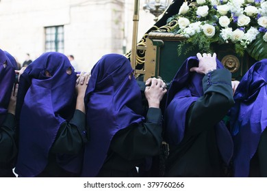 PONTEVEDRA, SPAIN - APRIL 3, 2015: A group of religious brothers, carry a heavy religious image during the celebration of Holy Week in the city.