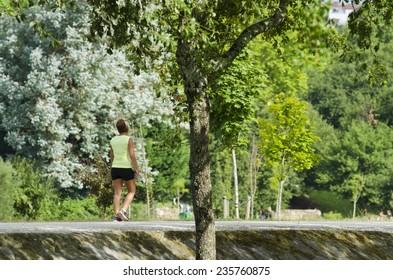Pontevedra, SPAIN - AUGUST 3, 2014: A woman walks with sportswear, for one of the parks, existing at the edge of Rio Lerez.