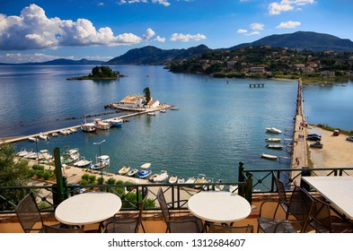 Pontikonisi and Vlacheraina Orthodox monastery seen from the hilltop of Kanoni on the island of Corfu, Greece. Beautiful summer landscape at a table in a cafe