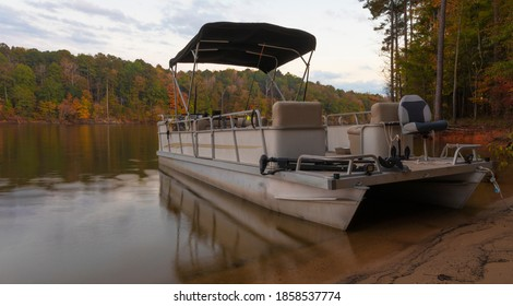 Pontoon boat beached on the shore of Falls Lake in Autumn