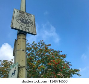 PONTYPRIDD, WALES - JULY 2018: A Neighbourhood Watch sign on a lamp post which is covered in green mildew.