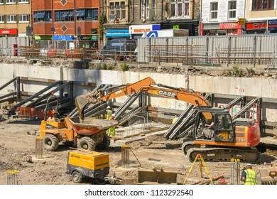 PONTYPRIDD, WALES - JUNE 2018: Excavator loading a dumper truck on the site of a major new office development in Pontypridd town centre