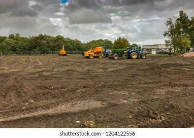 PONTYPRIDD, WALES - SEPTEMBER 2018: Contractor's plant undetaking work to improve the drainage on a sports pitch in Church Village near Pontypridd before reseeding the grass surface.