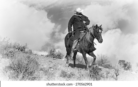 Pony Express Ridge Rider 1 in Black and White.  A lone cowboy in a black coat rides his horse down a mountain ridge with dramatic skies behind him.