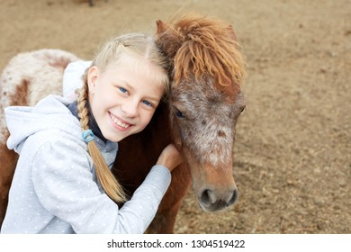 Pony and horsewoman - little girl hugging her best friend