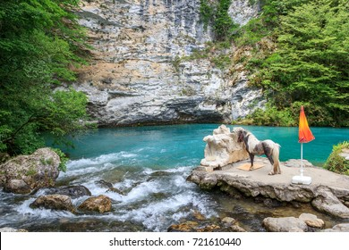 a pony stands in a gorge of an against a small blue lake, Abkhazia road to the Ritz