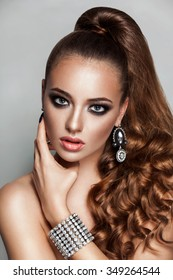 Ponytail hairstyle. Beauty brunette fashion model girl with long healthy curly brown hair and shiny jewelry. new year club make up.