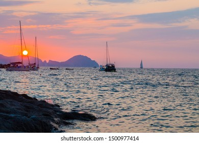 Ponza Island, Italy - August 2019: Sunset on little harbor of Ponza island in the summer season with boats and cliffs silhouette . Ponza, Italy