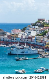 Ponza, Lazio  Italy - September 18 2021: The port of the Ponza island in summer. Coloured houses,  boats, ferry in the harbour of island of Ponza. Sunny day, blue water and fresh colours.