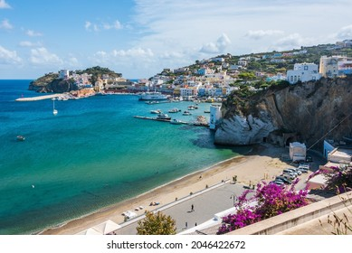 Ponza, Lazio  Italy - September 18 2021: The port of the Ponza island in summer. Coloured houses,  boats, ferry in the harbour of island of Ponza. People on a free beach along Via Dante Alighieri.