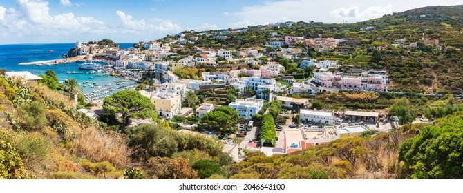 Ponza, Lazio, Italy - September 18 2021: Panoramic view of the port of the Ponza island in summer. Coloured houses,  boats, ferry in the harbour of island of Ponza. Sunny day, blue water, fresh color