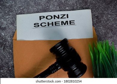 Ponzi Scheme text with document brown envelope and gavel isolated on office desk.