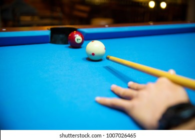 Pool balls on the blue felt pool table with player hands and pool cue stick. Indoor sports. sport and gambling concept. image for background, copy space and article. pocket billiard. cue sports.