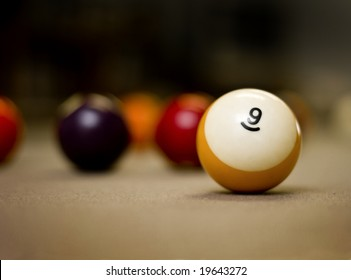 Pool balls on the table with shallow depth of field, focus on the nine ball