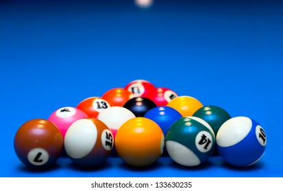 Pool balls triangle on blue billiard table, waiting to play.