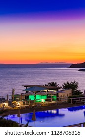 A pool and bar by the sea at sunset in summer in Piombino in front of the Elba Island, Italy