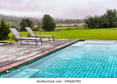 Pool Chairs with rice farm and mist