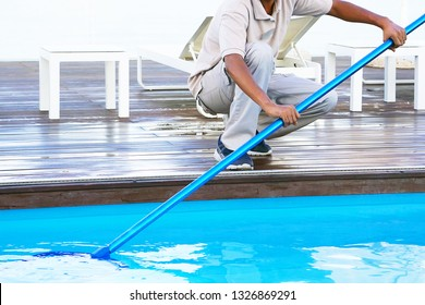 Pool cleaner during his work. Hand african hotel staff worker cleaning the pool.