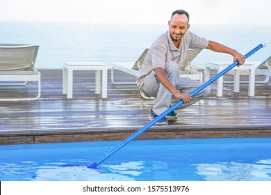Pool cleaner during his work. African hotel staff worker cleaning the pool.