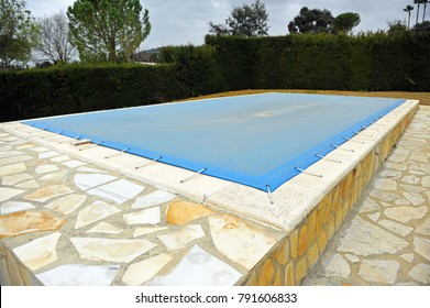 Pool covered with a blue tarp in winter to protect it and avoid risks