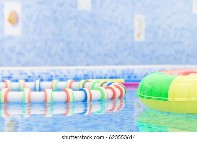 pool with floating buoys and toys and bright blue water for children