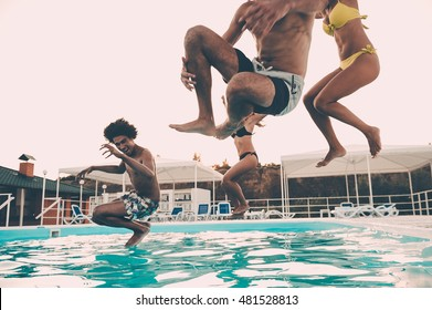Pool fun. Group of beautiful young people looking happy while jumping into the swimming pool together