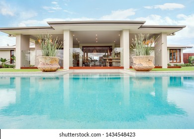 Pool overlooking the entrance of the house with two beautiful Front Door Planters complementing the view.