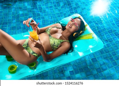 Pool party: Beautiful sexy tanned interracial girl posing while lying on an airbed in the pool, with a cocktail in her hand and yellow headphones, in a green bikini. Enjoyment.