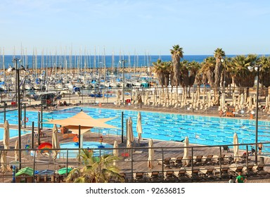 Pool with sea water for adult and children near yacht-club and palm tree oasis on Mediterranean sea background