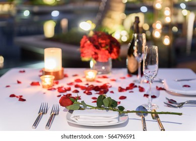Pool side Candlelight Dinner and Romantic Sunset Dining table setup for couple with bottle of champagne
