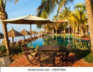 pool, sunbed, umbrellas on background of the sea and sky at dawn