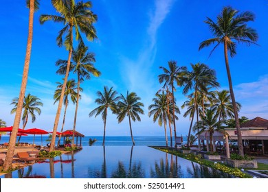 Pool surrounded by palm trees on the sea beach. On the edge of the pool red sun canopy. Rest of the Andaman Sea. Popular resort on the island of Koh Samui