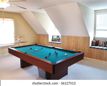 A pool table in a bonus room in a modern American luxury home. Two window seats in dormers are on the wall, and the balls are on the table waiting for a game.