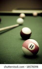 Pool table with a couple of balls and cue