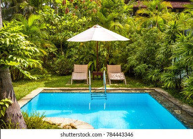 Pool with umbrella and beach beds at tropical hotel or vacation home. Beautiful swimming pool in courtyard. Chill out place with blue clean water in backyard. Nice garden in summer resort.