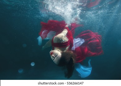In the pool underwater dancing girl, she in a red dress.