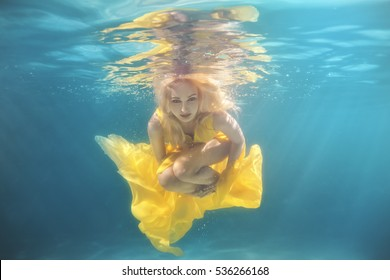In the pool underwater swim woman, she in a yellow dress.