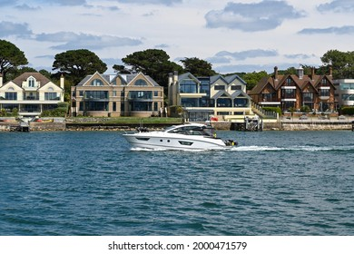 Poole, England - June 2021: Motorboat sailing past houses on the waterfront in the Sandbanks areas of Poole