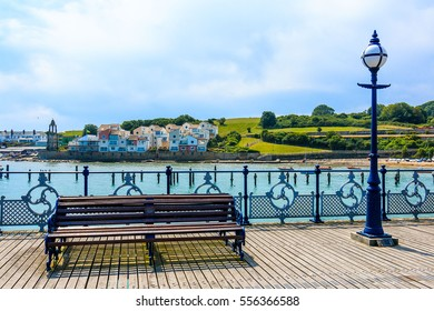 Poole Quay in Dorset with an old bench and background of village and grass